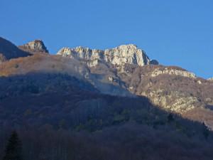 Върховете на планината се показват в синьо необятно небе ...